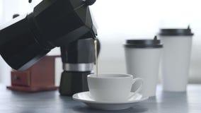 Koffie het Gieten in een Kop op een blauwe Houten Lijstachtergrond met witte koffiekoppen, bonenmolen, geiser stock footage