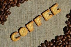 Koffie Het woord van de eetbare brieven ligt op het grijze canvas Stock Afbeelding
