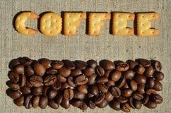 Koffie Het woord van de eetbare brieven ligt op het grijze canvas Stock Foto
