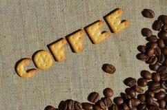 Koffie Het woord van de eetbare brieven ligt op het grijze canvas Stock Afbeeldingen