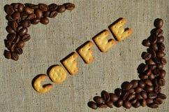 Koffie Het woord van de eetbare brieven ligt op het grijze canvas Royalty-vrije Stock Afbeeldingen