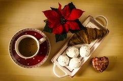 Koffie, koekjes, één croissant en een Kerstmisbloem Royalty-vrije Stock Afbeeldingen