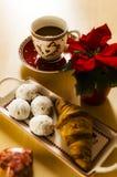 Koffie, koekjes, één croissant en een Kerstmisbloem Stock Foto's
