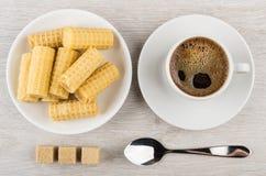 Koffie in kop, stukken van suiker, wafeltjebroodjes in schotel stock foto's