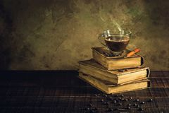 Koffie in kopglas op oude boeken en oude houten vloer royalty-vrije stock foto