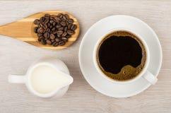 Koffie, kruikmelk en houten lepel met koffiebonen Royalty-vrije Stock Foto's