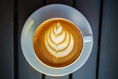Koffie latte kunst op de houten lijst stock foto's
