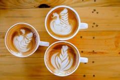 Koffie latte kunst op houten lijstboom stock afbeeldingen