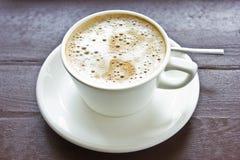 Koffie latte met melkachtige schuim en bellen in wit porseleincu stock afbeeldingen