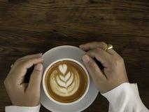 koffie latte met mooie lattekunst op hand stock afbeeldingen