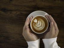 koffie latte met mooie lattekunst op hand royalty-vrije stock afbeeldingen
