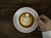 koffie latte met mooie lattekunst op hand stock afbeelding