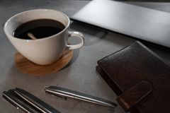 Koffie, lepel, laptop, notitieboekje en pennen op concrete lijst stock afbeeldingen