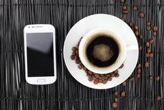 Koffie met bonen en slimme telefoon stock afbeelding