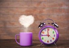 Koffie met de stoom van de hartvorm en wekker royalty-vrije stock foto
