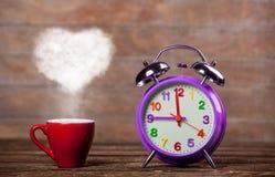 Koffie met de stoom van de hartvorm en wekker stock afbeelding