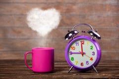 Koffie met de stoom van de hartvorm en wekker stock afbeeldingen