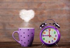 Koffie met de stoom van de hartvorm en wekker stock foto's