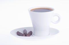 Koffie met drie chocolade op een schotel stock foto's