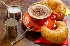 Koffie met geschuimde melk, cacao en croissants Stock Afbeeldingen