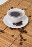 Koffie met koffiebonen op bamboe Stock Foto