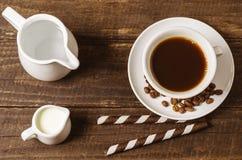 Koffie met melk en wafeltjebroodjes op een houten achtergrond stock afbeeldingen