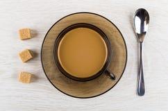 Koffie met melk in kop, suiker en lepel op lijst stock fotografie