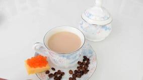 Koffie met melk naast suikerkom en rode kaviaar met kaas stock videobeelden
