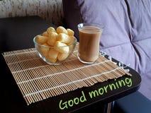 Koffie met melk van een stelaannuyukop en luchtige koekjes op een bamboemat met een wens van goedemorgen Close-up stock fotografie