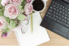Koffie met notitieboekje, bloem, potlood, oogglazen op hout backgroun Stock Foto's