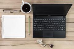 Koffie met notitieboekje, bloem, potlood, oogglazen op hout backgroun Stock Afbeelding