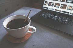 Koffie op concrete lijst met gouden lepel en laptop met koffiebeelden als achtergrond royalty-vrije stock afbeelding