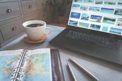 Koffie op concrete lijst met reiskaart, pennen en laptop met reisbestemmingen als achtergrond royalty-vrije stock foto's