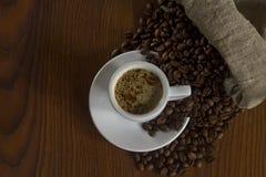 Koffie op een houten lijst en koffiebonen van een zak Royalty-vrije Stock Foto