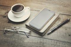 Koffie, telefoon, notitieboekje, pen en glas Royalty-vrije Stock Afbeeldingen