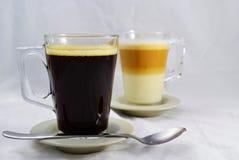 Koffie wit en zwart met een theelepeltje - zwarte vooraan Royalty-vrije Stock Foto's