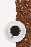 Koffie in witte kop op schotel geplaatste cofeebonen Royalty-vrije Stock Afbeeldingen