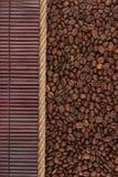 Koffiebonen die op donkere bamboemat liggen, voor menu Stock Foto