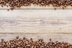 Koffiebonen die op een houten achtergrond 1 worden verspreid stock afbeeldingen