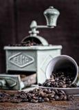Koffiebonen die uit kop met molenachtergrond komen royalty-vrije stock afbeelding