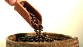 Koffiebonen die van houten met de hand gehouden scooper gieten stock footage