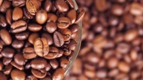Koffiebonen in een close-up van de glasbeker Het vertroebelen van koffiebonen stock footage