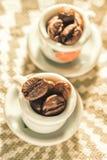 Koffiebonen in een klein mooi close-up van porseleinkoppen Stock Foto's