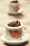 Koffiebonen in een klein mooi close-up van porseleinkoppen Stock Afbeeldingen