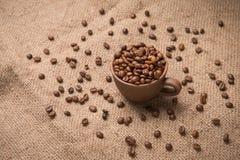 Koffiebonen in een kop bij het ontslaan Stock Afbeelding