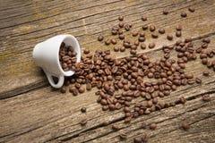 Koffiebonen in een kop op de raad Royalty-vrije Stock Afbeeldingen