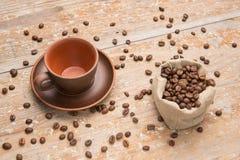 Koffiebonen in een kop op de raad Stock Afbeeldingen