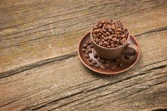 Koffiebonen in een kop op de raad Royalty-vrije Stock Foto's