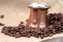 Koffiebonen en de traditionele Turkse pot van de koperkoffie op een jute Royalty-vrije Stock Afbeeldingen