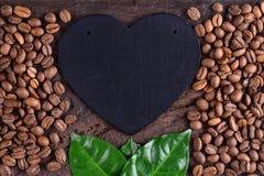 Koffiebonen en groene bladeren met hart op een oud houten bureau Liefde aan koffieachtergrond Liefde en koffie Stock Fotografie